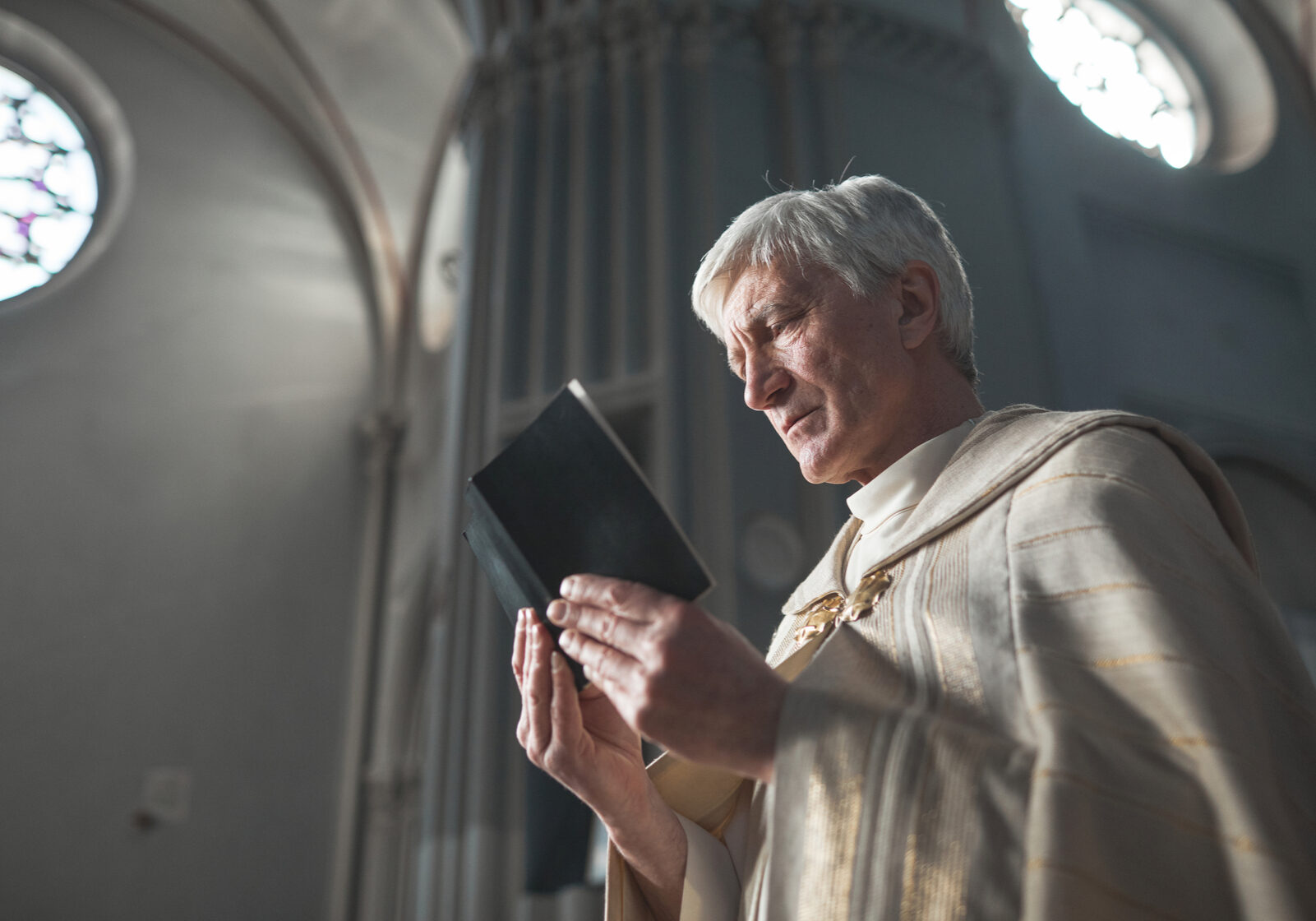 Senior priest in formal costume reading prayers while holding ceremony in the church